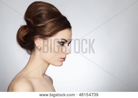 Profile portrait of young beautiful woman with stylish hair bun