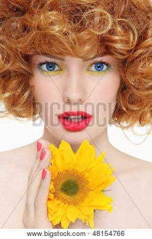 Portrait of young beautiful girl with curly hair and sunflower in her hands