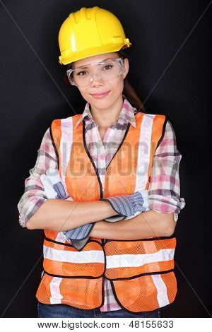 Construction worker with safety vest, glasses and hardhat portrait on black background. Portrait of young asian chinese / caucasian model