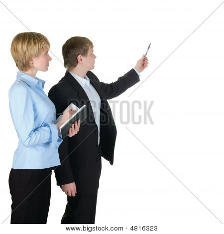 Portrait Of Businessman Pointing At Wall With Woman Near By.