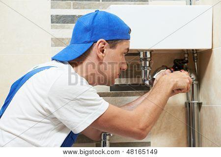 Trabajador joven plomero trabajando con llave en el sistema de instalación sanitaria de lavabo