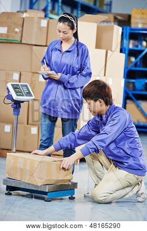 two young chinese workers in uniform with weight  scales and box at warehousing system