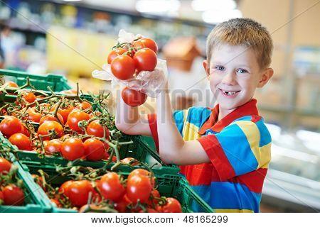 niño niño durante compras con verduras rojo tomate maduro en el supermercado