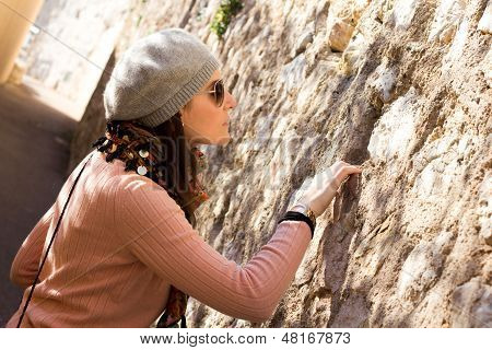 Woman Looking Into A Hole In A Stone Wall