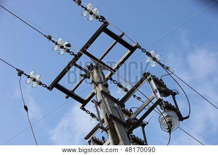 Overhead Electricity Pole Against A Blue Sky