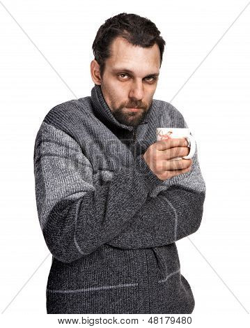 Sick man, affected by cold, dressed in grey sweater holding a cup of tea in hands