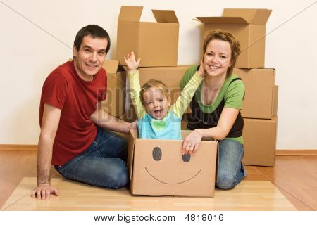 Happy Family In Their New Home Sitting On The Floor