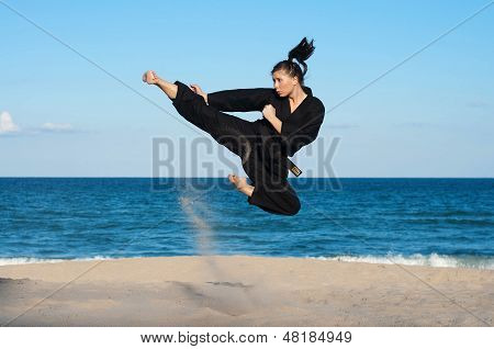 Young Female Taekwondo Athlete Kicking Midair