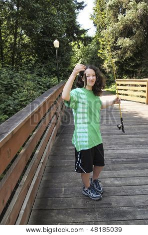 Young Girl With Small Fish On Wooden Bridge