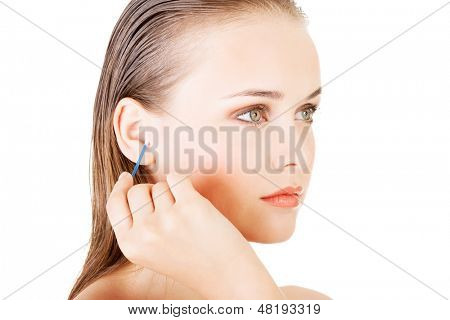 Woman face closeup while cleaning up an ear with a swab, over white.
