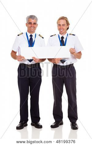 smiling airline pilots holding blank banner on white background
