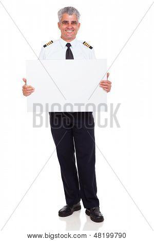 smiling senior airline pilot captain holding white board on white background