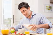 stock photo of breakfast  - Happy Young Man Pouring Milk Into Bowl For Breakfast - JPG