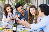 stock photo of lunch  - Group Of Happy Young Friends Toasting Wine Glass Outdoor While Having Lunch - JPG