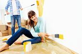 stock photo of wall painting  - renovation diy paint couple in new home painting wall - JPG