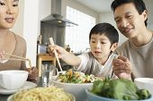 picture of chopsticks  - Young parents watching son trying to use chopsticks at dining table - JPG