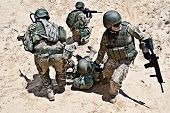 stock photo of battlefield  - Squad of soldiers evacuate the injured fellow in arms in the desert - JPG