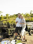 Smiling couple on picnic during safari with jeep in the background