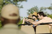 stock photo of safari hat  - Tourists on safari pointing at view with blurred guide in foreground - JPG
