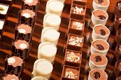 foto of truffle  - Rows of artisan chocolate truffles lined up by type on a wooden table - JPG