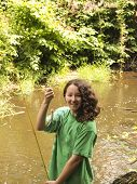 stock photo of brook trout  - Vertical photo of young girl smiling while holding up small trout with stream and trees in background - JPG