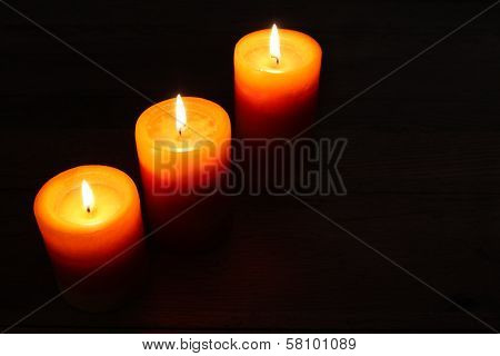 Three burning candles on a dark background