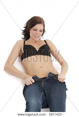 Beautiful brunette woman struggling to fit into tight jeans