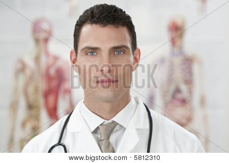 Male Doctor In Hospital With Human Anatomy Charts