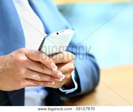 Young beautiful woman writes an SMS to your mobile phone