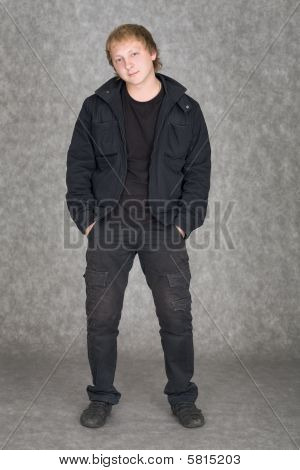 Young Guy In A Jacket Standing On A Grey Background