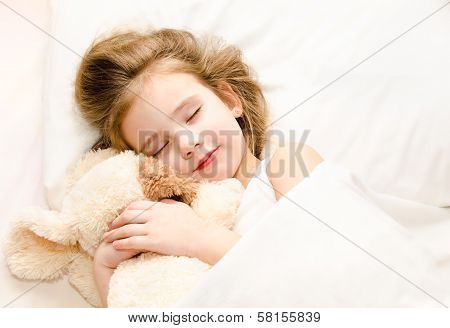 Little Girl Sleeping In The Bed With Her Toy