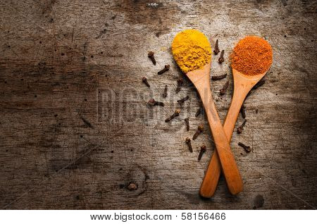 Spices in wooden spoons on wooden background