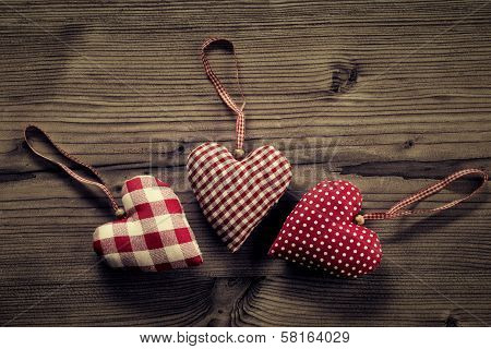 3 pieces of fabric hearts polka dots plaid on wood background
