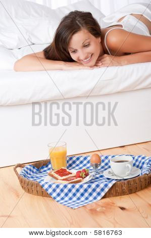 Smiling Woman In Bed Watching Homemade Breakfast