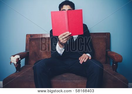 Businessman On Sofa Is Reading
