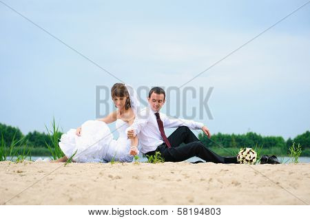 Loving Wedding Couple Sitting Near Water And Strew Sands