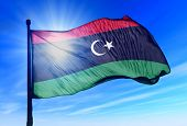 image of libya  - Libya flag waving on the wind on the sky - JPG