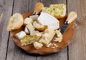 picture of brie cheese  - Cheese Board with Delicious Camembert Brie Parmesan Cheese and Garlic Bread and Cheese Knifes closeup on Rustic Wood background - JPG
