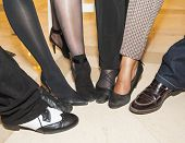 stock photo of semi-circle  - Selection of footwear and legwear on peoples legs at a party in semi circle for fun - JPG