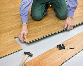 stock photo of laminate  - Man makes laying laminated panels color of wood - JPG