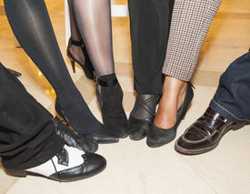 foto of semi-circle  - Selection of footwear and legwear on peoples legs at a party in semi circle for fun - JPG