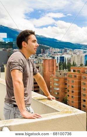 young man looking at Quito city view from balcony