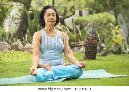 Asian Senior Woman Meditating For Yoga Outside