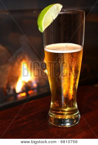 Refreshing beer with lime, fireplace background