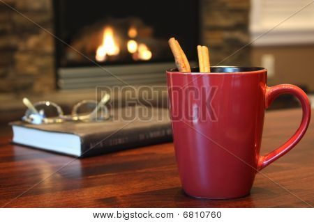 Hot cinnamon tea in dark red mug, landscape view