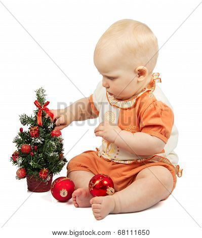 Baby decorates christmas tree with red spheres