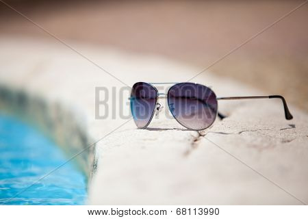 Sunglasses over swimming pool vacation concept