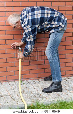 Man Repairing Leaky Garden Hose Spigot
