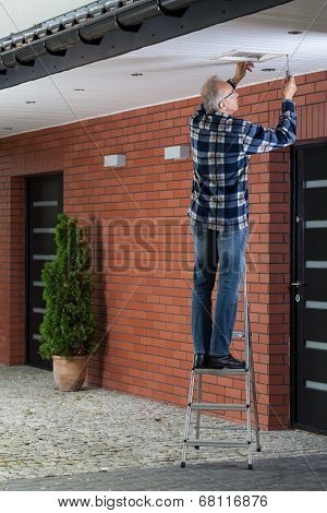 Man Standing On The Ladder And Tightening Ventilation Grille