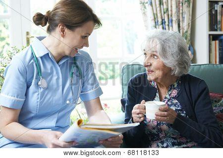 Nurse Discussing Medical Notes With Senior Woman At Home